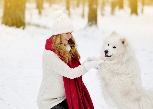 Bastante joven en snowy winter forest park caminando jugando con su perro samoyedo blanco estacional