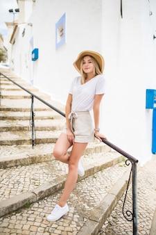 Bastante joven con sombrero camina por la escalera al aire libre en la calle de verano.