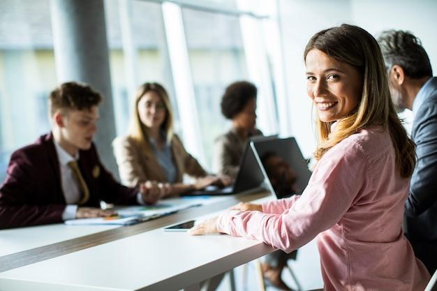 Bastante joven sonriendo durante la exitosa reunión de negocios en la oficina moderna