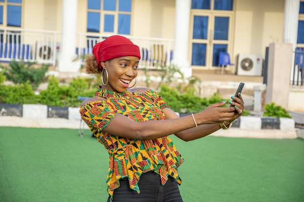 Bastante joven sonriendo y usando su teléfono móvil al aire libre