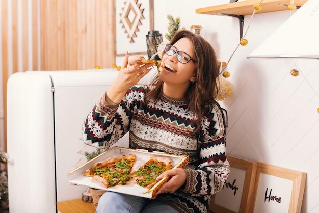 Bastante joven sosteniendo una caja de pizza está comiendo una rebanada.