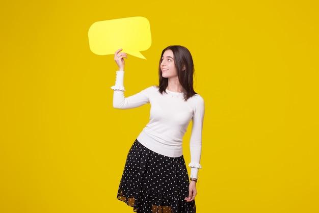 Bastante joven está sosteniendo un discurso de burbuja sobre fondo amarillo.