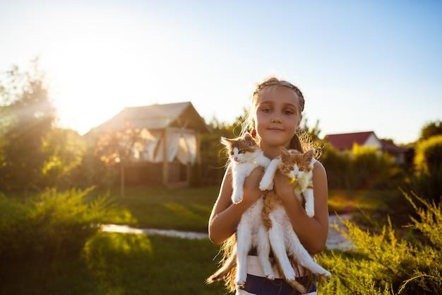 Bastante joven sosteniendo gatitos, sonriendo