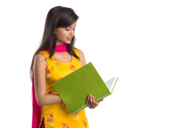 Bastante joven sosteniendo el libro y posando sobre fondo blanco.