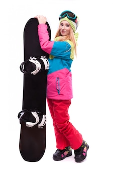 Bastante joven en traje de esquí y gafas de esquí tienen snowboard