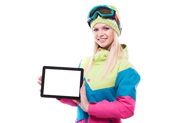 Bastante joven en traje de esquí y gafas de esquí tienen tableta vacía