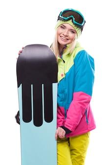 Bastante joven en traje de esquí mantenga snowboard