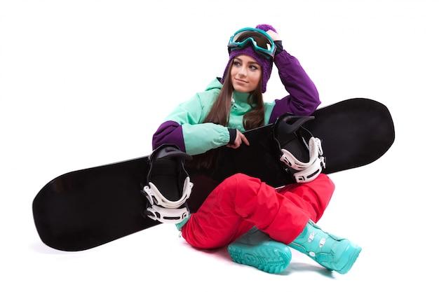 Bastante joven en traje de esquí púrpura emplazamiento con las piernas cruzadas