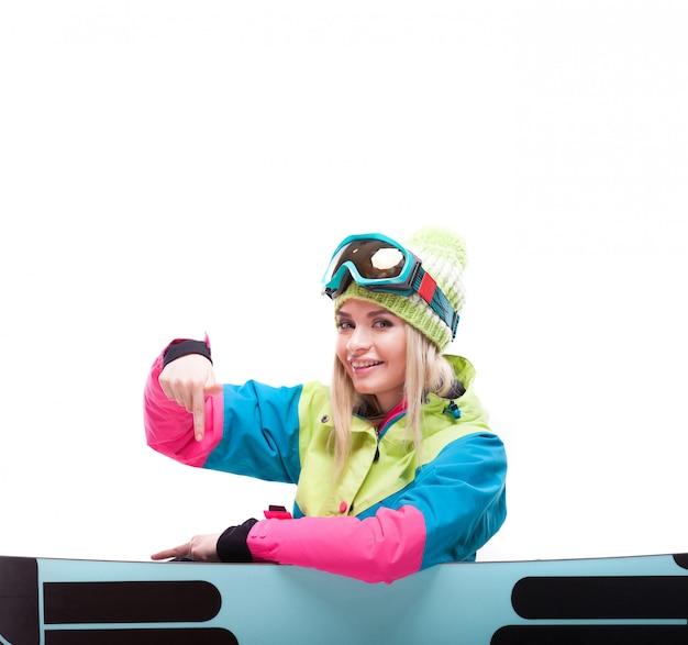 Bastante joven en traje de esquí sentarse cerca de snowboard