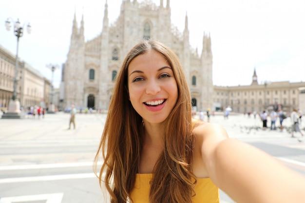 Bastante joven turista toma autorretrato en la plaza de la catedral de milán, italia.