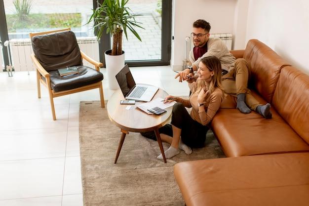 Bastante joven usando laptop y joven usando tableta digital mientras está sentado en el sofá en casa