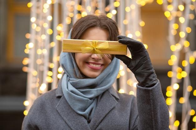 Bastante joven vestida con abrigo de invierno y bufanda sosteniendo una caja de regalo con un lazo en la calle