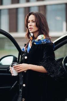 Bastante joven vestida con un abrigo negro de moda mientras mantiene el café y está de pie cerca del coche. concepto de ciudad de moda