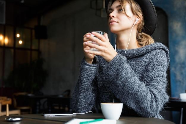 Bastante joven vestida con suéter y sombrero sentado en la mesa de café en el interior, escuchando música con auriculares, tomando café