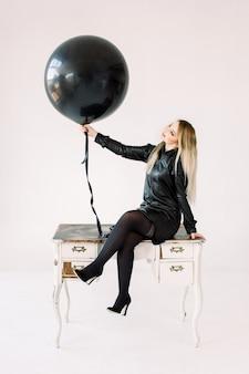 Bastante joven en vestido de cuero negro con gran globo de aire negro, sentado en los muebles de mesa vintage ornamento blanco real con cajones, aislado sobre fondo blanco.