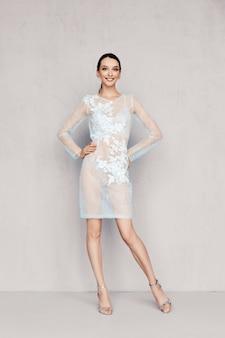 Bastante joven en vestido de tul transparente con encaje posando cerca de la pared