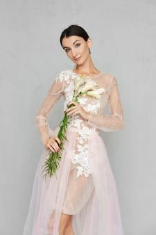 Bastante joven en vestido de tul transparente con encaje posando con flores en la mano