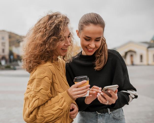 Bastante jovencitas revisando un teléfono juntos