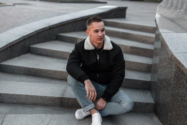 Bastante lindo joven en jeans con estilo en zapatillas de cuero de moda en chaqueta de moda negra descansa sentado en una escalera de piedra vintage al aire libre