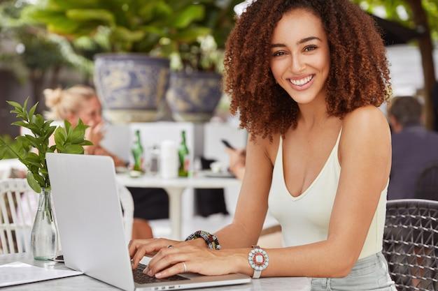 Bastante modelo de mujer afroamericana teclados algo en una computadora portátil, conectada a internet inalámbrico gratuito en la cafetería, escribe un nuevo artículo para su blog