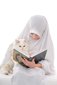 Bastante musulmana y gato leyendo el libro sagrado del corán