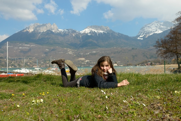 Bastante preadolescente está tumbado en la hierba verde