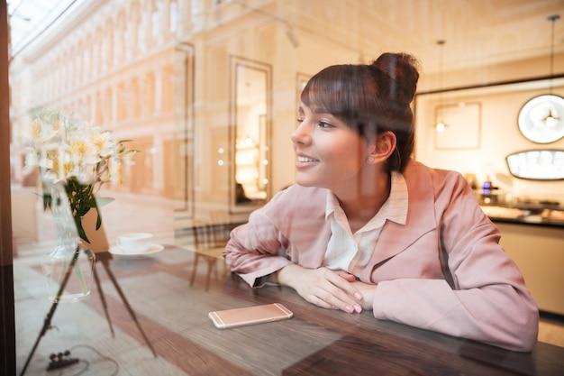Bastante soñando mujer joven sentada en la mesa de café