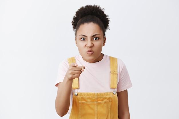 Bastardo. retrato de mujer enojada y enojada reconociendo al hombre que robó el bolso, señalando con ira y disgusto, frunciendo el ceño, frunciendo los labios y doblando la cabeza, posando sobre una pared gris