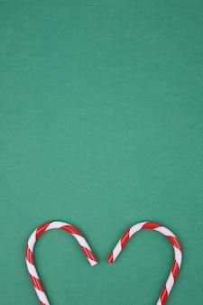 Bastón de caramelo en forma de corazón sobre fondo verde