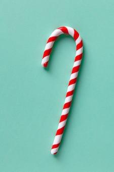 Bastón de caramelo de menta de navidad sobre fondo turquesa pastel.