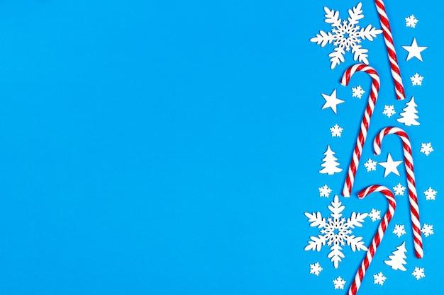 El bastón de caramelo de navidad mintió uniformemente en fila sobre fondo azul con copos de nieve decorativos y estrellas. vista plana y superior