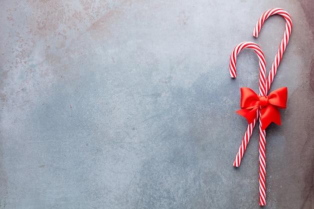 Bastón de caramelo de navidad mintió uniformemente en fila sobre fondo azul.