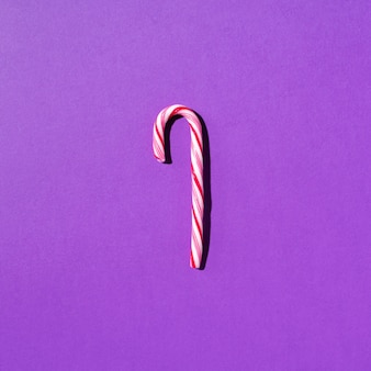 Bastón de caramelo de navidad sobre fondo violeta