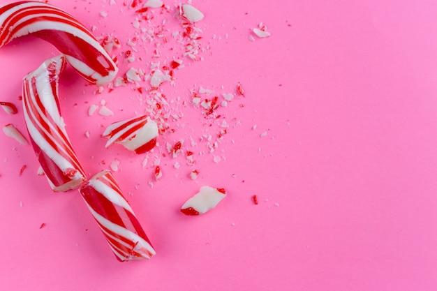 Bastón de caramelo quebrado en fondo rosado. cerca de la foto