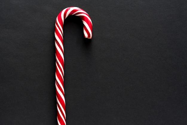 Bastón de caramelo tradicional sobre fondo negro. año nuevo y navidad