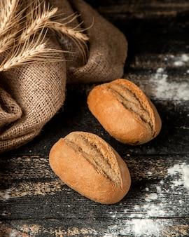 Bastón de pan con corteza crujiente y harina en la mesa