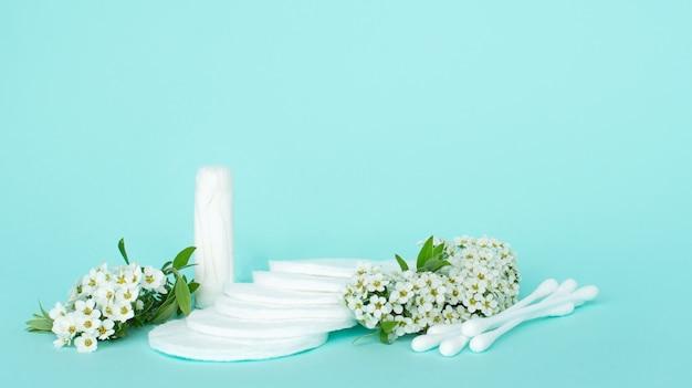 Bastones y bastoncillos de algodón para orejas y desmaquillante de algodón sobre fondo turquesa con pequeñas flores blancas.