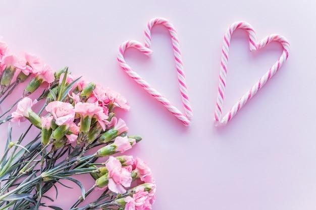 Bastones de caramelo en forma de corazón con flores