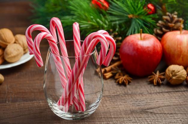 Bastones de caramelo de menta y otras decoraciones de navidad sobre fondo de madera