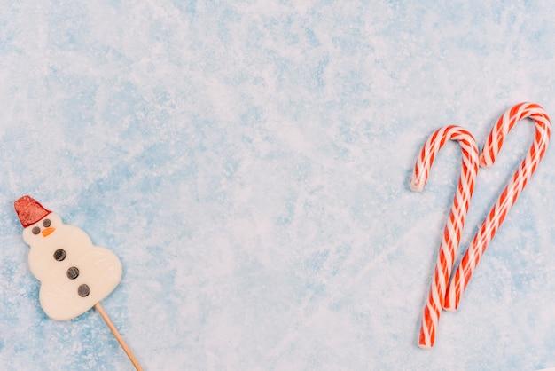 Bastones de caramelo y piruleta en forma de muñeco de nieve.