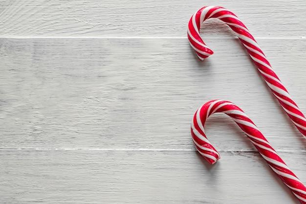 Bastones de caramelo tradicional sobre fondo de madera. año nuevo y navidad