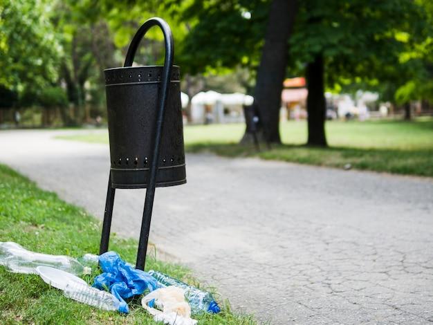 Basura de basura plástica en hierba cerca de cubo de basura en el parque