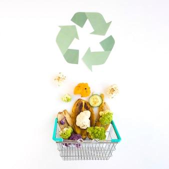 Basura orgánica en la cesta cerca del logotipo de reciclaje