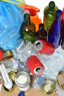 Basura que consiste en latas, botellas de plástico, botellas de vidrio, cajas de cartón, tetrabrik, latas y bulbos.