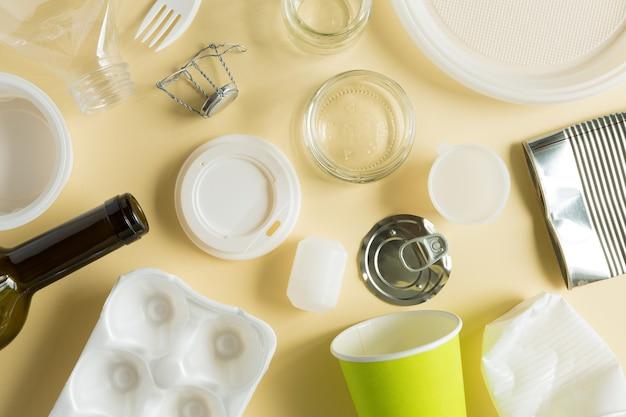 Basura para reciclaje de diversos materiales, plástico, metal y otros planos sobre fondo de papel amarillo