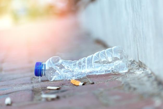 Basura en el suelo de una ciudad con colillas de cigarrillos y botella de plástico usada. concepto ecológico.