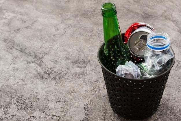 Basurero de basura con basura en superficie gris