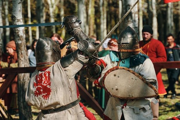 Batalla de caballeros con armadura sobre espadas frente a la audiencia.