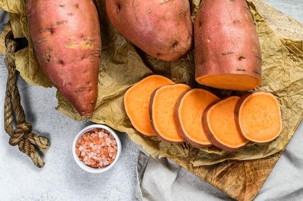 Batatas en una tabla de cortar, ñame.