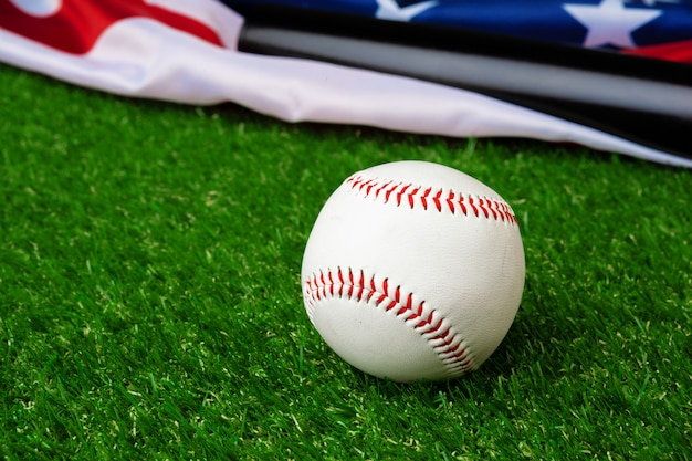 Bate de béisbol y pelota con bandera americana sobre hierba